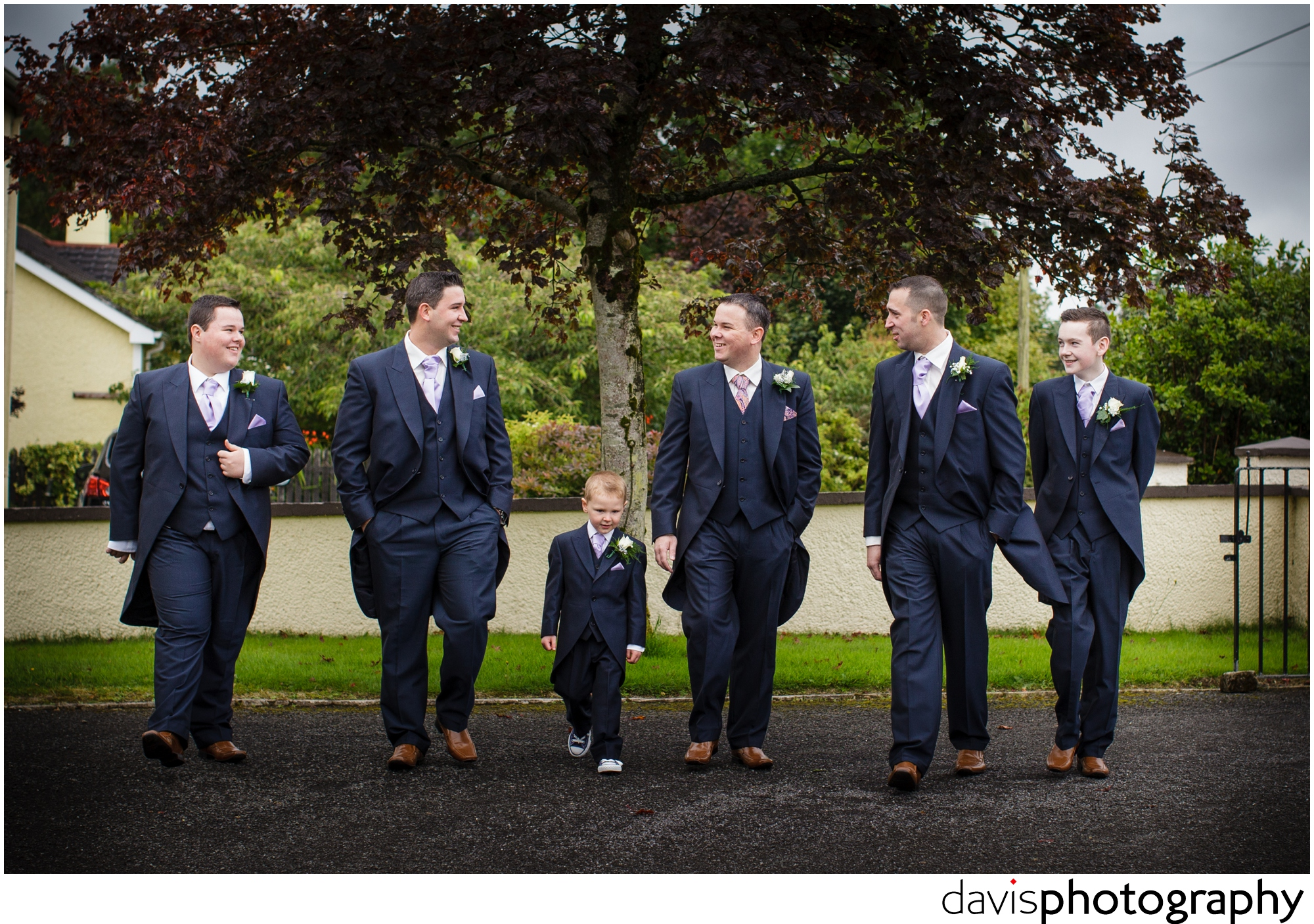 groom walks to church with his best man groomsman and pageboy